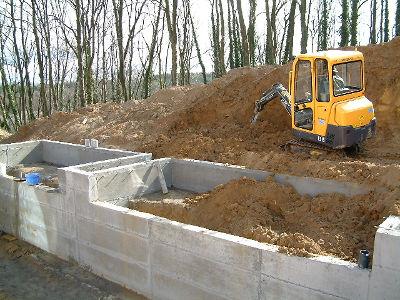 Opération de remblayage de la terre à l'extérieur des murs du bassin naturel